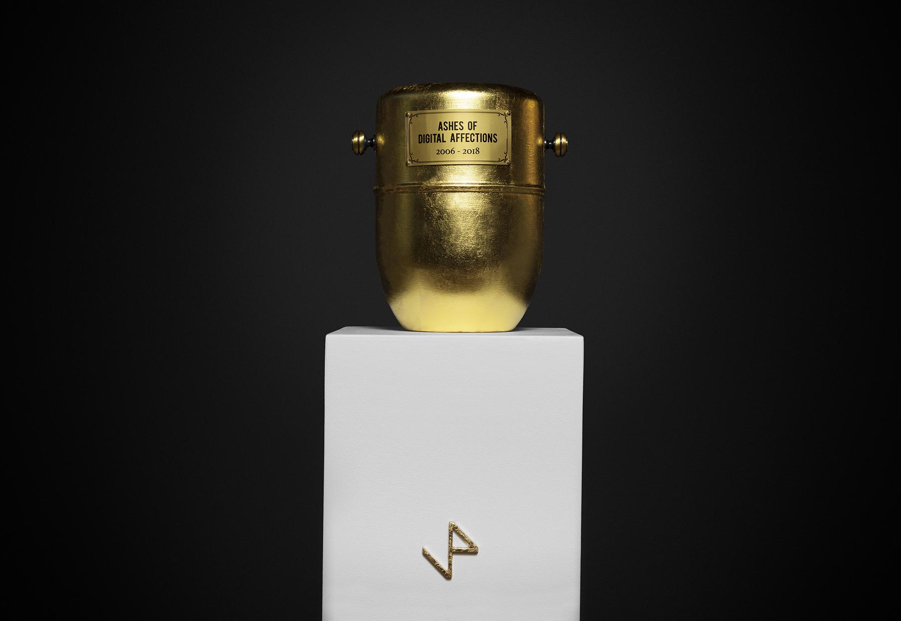 Ceneri di affetti digitali / Ashes of digital affections-33cm x 33cm x 125cm-Urna cineraria, ceneri di dispositivi digitali, oro zecchino, ottone, legno, stampa uv-©2018 – Edition of 1